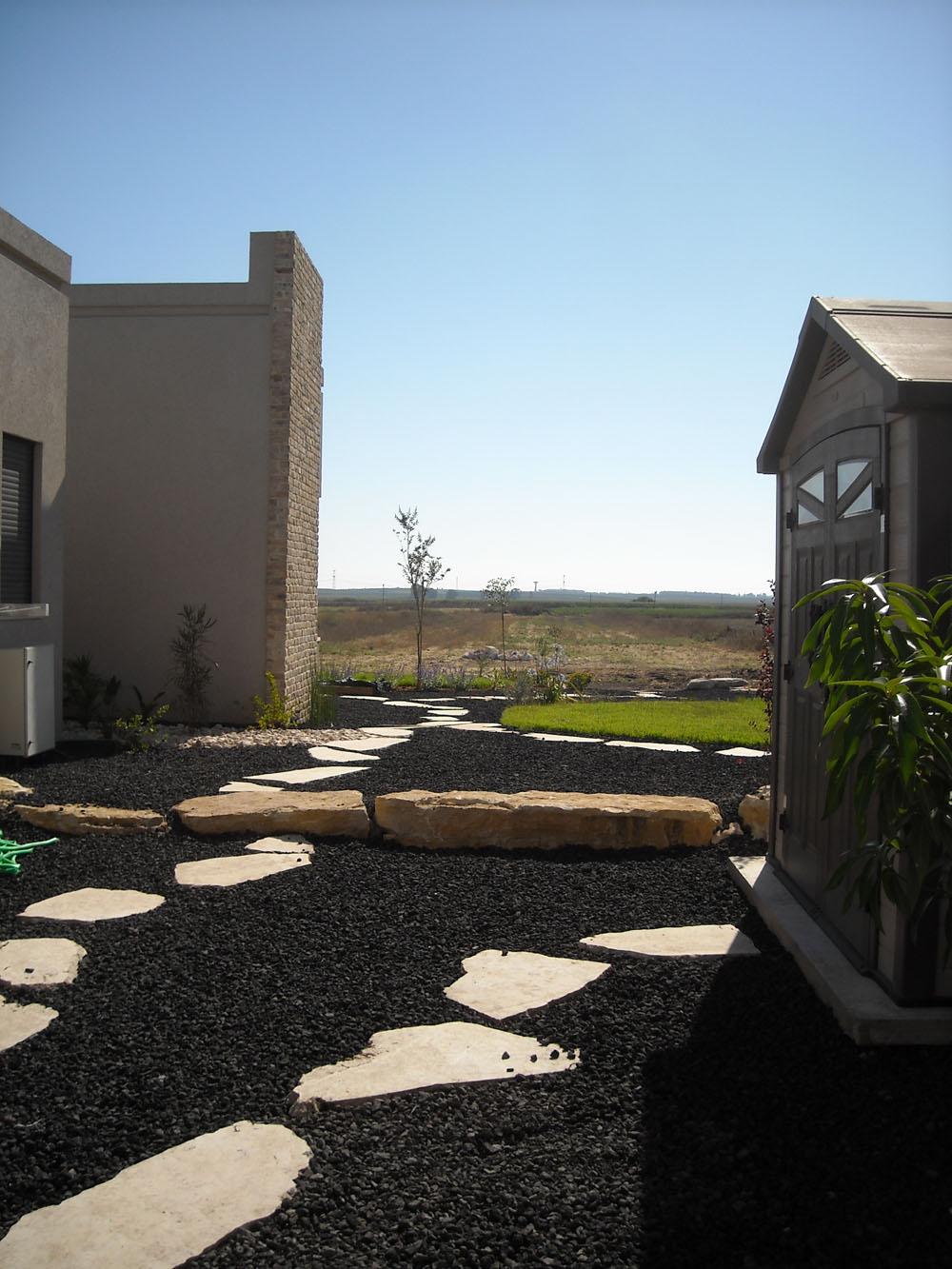 מבט מהחצר הפנימית אל החצר האחורית. שימוש נרחב בטוף שחור ואבני מדרך לבנות.